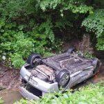 """Un autoturism s-a răsturnat pe DN 74, în pârâul """"Valea Cerbului"""", după ce șoferul nu a adaptat viteza la condițiile de drum"""
